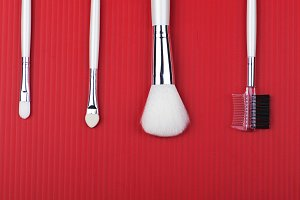 Makeup tools on red background.