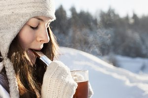 girl drinking tea over winter nature