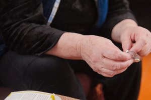 Hands of elderly woman with pills medication packages - pension healthcare