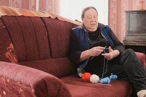 Senior lady sitting on the sofa and knits colourful wool - pensioners hobby at home