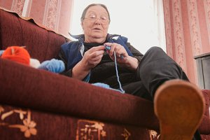 Old woman pensioner knits wool socks sitting on the sofa - elderly lady hobby at home
