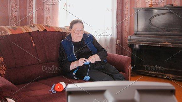 Old lady at home - senior woman watching television and knits wool socks