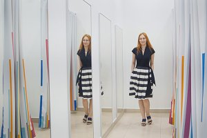 Girl with red hair trying dress near mirror in fitting room - shopping concept