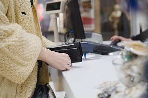 Woman paying by credit card in dress store - shopping concept