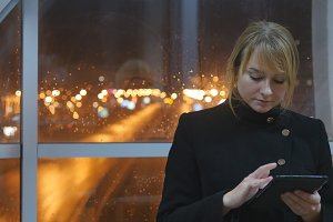 Young woman use tablet in the evening indoor. Portrait of attractive girl with tablet in hands. Close up. Beautiful blur night city traffic at window at background