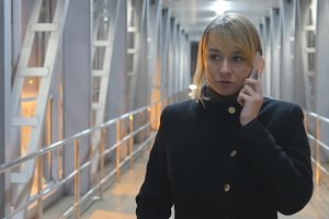Young woman talking on the phone and walk in the night indoor. Portrait of attractive girl speaking on cellphone. Close up
