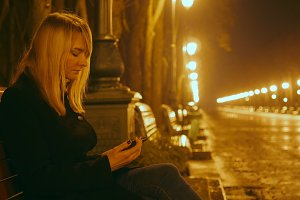 Young beautiful girl sits on a bench in a night park and using a tablet. Alley and lights in the background. Close up