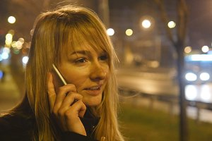 Young woman talking on the phone in the evening outdoor. Portrait of attractive girl speaking on cellphone. Close up. Beautiful blur night city at background
