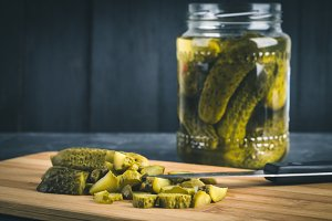 Cucumbers or pickled gherkins with a knife on a wooden cutting board. Blue gray background. Bank with cucumbers.