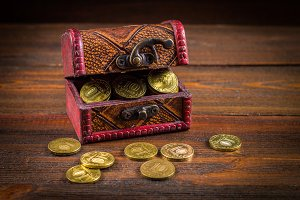 A chest with gold coins on a wooden background. Clover leaves. St.Patrick 's Day.