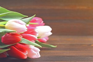 Happy mother's day. Tulips on a brown wooden background