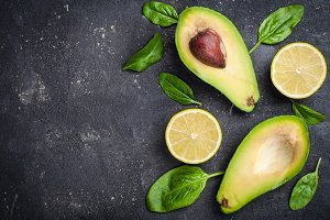 Avocado with spinach leaves and lime