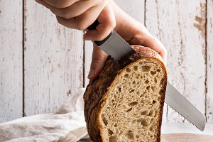 Slicing the loaf of sourdough bread
