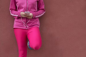 female athlete with the phone on the street