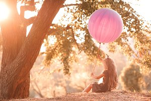 Girl with balloon in sun light