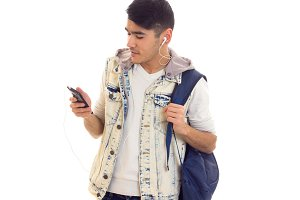 Young man with backpack, smartphone and headphones
