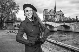 cheerful young tourist woman on embankment in Paris, France