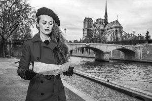 traveller woman near Notre Dame de Paris in Paris looking at map