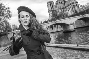 tourist woman taking selfie with phone on embankment in Paris