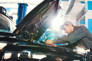 Mechanic in car service - repairing in engine compartment for luxury SUV