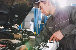 Mechanic in overalls checks level of engine oil in the car - automobile service repairing