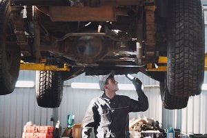 Mechanic with thr lamp is checking the bottom of SUV car in garage automobile service, wide angle