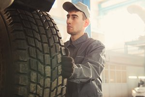 Car service - a mechanic checks the wheel of SUV, wide angle