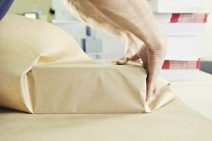 Man's hands packing boxes of sellotape in printing industry