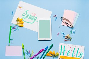 Blue flat lay with gadget stationery glasses spring lettering
