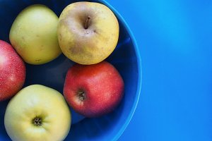 yellow and red apple fruit food over blue with copy space
