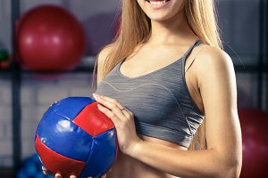 Young fitness girl with medicine ball in gym