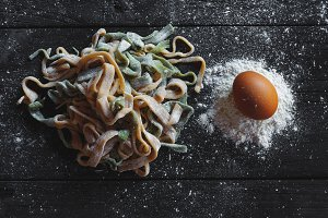 Top view on raw homemade pasta with flour and raw egg over old wooden table