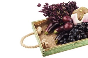 Set of different violet fresh raw vegetables and fruits in the wooden tray