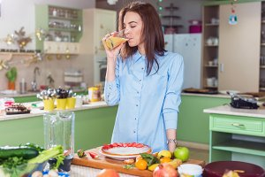Slim young woman standing in kitchen drinking fresh juice