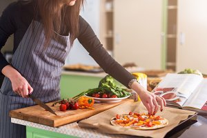 Cropped image of woman putting sliced vegetables on pizza top cooking in apron in the kitchen