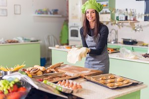Happy female baker preparing dough to make pastry in bakery.