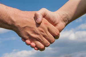 Man's handshake against a blue cloudy sky