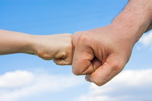 The fist of the child touches the male fist against the sky