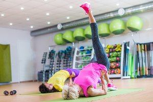 Fit athletic female doing single leg bridge exercise on mats at group classes in gym against bright sport equipment