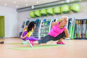 Muscular female fitness women doing stretching exercise indoors in sports club