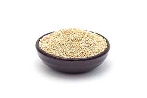 Ceramic bowl with healthy quinoa seeds isolated on white