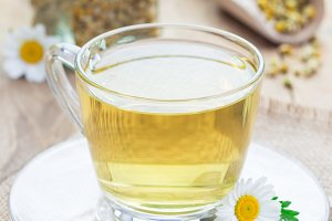 Chamomile tea in glass cup, chamomile flowers and dry tea on background, vertical