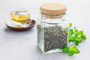 Dry herbal mint tea in a jar with cup of tea on background, horizontal
