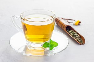 Herbal mint tea in a glass cup with tea scoop on background, horizontal