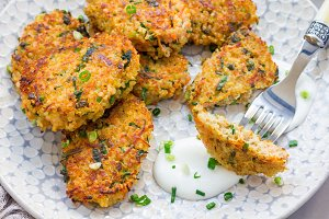 Vegetarian quinoa, carrot, coriander and green onion fritters served with yogurt on plate, horizontal
