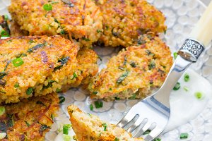 Vegetarian quinoa, carrot, coriander and green onion fritters served with yogurt on plate, vertical