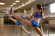 Female with nice body doing stretches a the gym