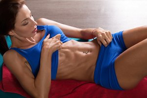 Muscular woman doing abs crunches in gym.