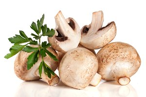 A bunch of champignon mushrooms with leaf parsley isolated on white background