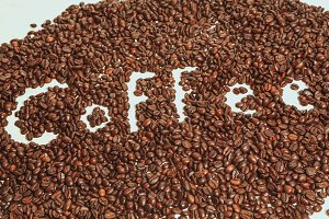 The words coffee written against scattered natural coffee